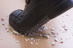 Foot crushing candy cane. Closeup of man's black dress shoe stepping and shattering Christmas candy cane on wood floor Royalty Free Stock Photos