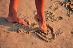 Foot drawing heart in sand. A woman drawing a heart in the sand with her toe and a heart tattoo on her foot Royalty Free Stock Photo