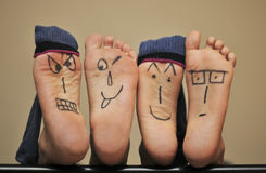 Foot faces. Faces expressions panted in under foots Stock Photography