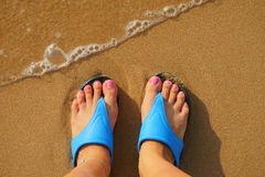 Foot in flip flops on the beach Stock Images