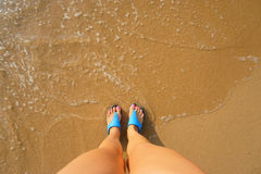 Foot in flip flops on the beach Royalty Free Stock Photos