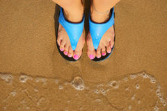 Foot in flip flops on the beach Royalty Free Stock Image