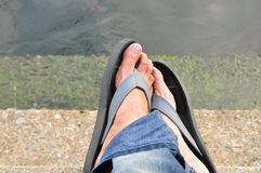 Foot and flipflops. Beside the river in the relaxing time royalty free stock image