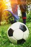 Foot with footbal boots on the ball Stock Photos