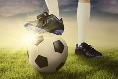 Foot of football player and ball at the meadow Stock Image