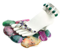 Foot with gemstones. Foot display form decorated with jewelry, standing on colorful gemstone pendants Royalty Free Stock Image
