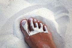 Foot girl with white pedicure in the sand Royalty Free Stock Photos