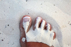 Foot girl with white pedicure in the sand Stock Photography
