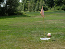 Foot Golf Putt. A soccer ball sits next to the cup and flag on a foot golf putting green Stock Image