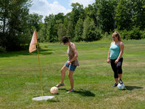 Foot Golf Putt. A young lady putts a soccer ball on a foot golf green while a partner watches Royalty Free Stock Photo