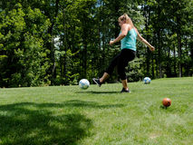 Foot Golf Tee Shot. A young woman is shown kicking a soccer ball at a foot golf tee off stock images
