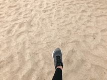 The foot in the gray boot shoe makes a step against the background of a natural loose yellow golden beautiful warm beach sand royalty free stock image