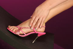 Foot in hand. Beautiful pink shoe on foot with hand wrapped at her ankle fingers well manicured Stock Photos