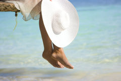Foot, hat and sea. Girl sitting on the beach tree overwhelming the waters with white hat Stock Image