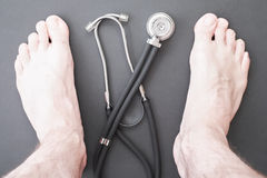 Foot health. Male feet with a stethoscope between them for your podiatry, podology and healthy feet concepts Royalty Free Stock Image