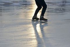 Foot ice-skating person on the rink in the sunlight