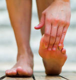 Foot are important to be healthy, massage foot on the tiptoe. Wooden floor Royalty Free Stock Image