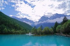 Blue lake at the foot of snow mountain stock photos