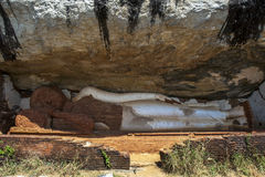 The 48 foot long sleeping Buddha statue built under a cliff face at the Pidurangala Temple at Sigiriya in Sri Lanka. This is the largest brick and mortar Stock Image