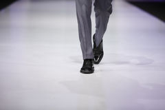 Foot of male model on catwalk. Foot of male model in gray trousers and black shoes on catwalk Stock Photography