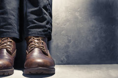 Foot man,black jeans, leather shoes on background concrete wall Stock Photos