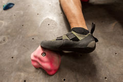 Foot of man exercising at indoor climbing gym Stock Photos