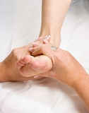 Foot massage. Female hands giving a healthy foot massage royalty free stock photo