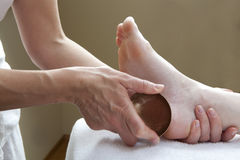 Foot massage with bronze bowl Royalty Free Stock Photos