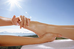 Foot Massage Concept. Woman legs get foot massage with blue sky background. This is spa concept royalty free stock image