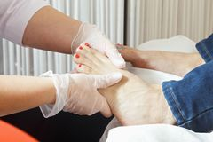Foot massage. Masseuse hands making foot massage. Horizontal closeup shot Stock Photo