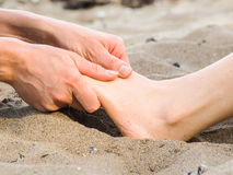 Foot massage in sand, male and female caucasian. Foot massage on a beach in sand, male and female caucasian Royalty Free Stock Photography