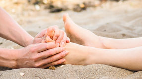 Foot massage in sand, male and female caucasian. Foot massage on a beach in sand, male and female caucasian Royalty Free Stock Photos