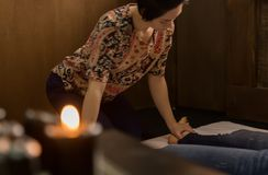 Foot massage in thai studio. Professional therapist giving traditional Thai massage.  Royalty Free Stock Photography