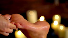Foot massage therapy on candle burning background. 4k.