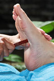 Foot massage by wood stick Royalty Free Stock Photography