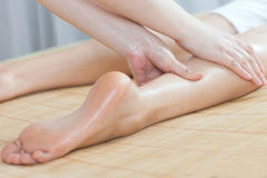 Foot massage for young lady in spa salon. A young women getting foot massage in spa salon, indoors Stock Photo