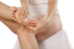 Foot massaging. Woman sitting and massaging her tired foot Stock Images