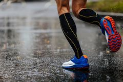 Foot men runner in compression socks. Running on rain asphalt on water royalty free stock photo