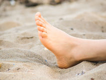 Foot of one unrecognizable caucasian person resting in sand. With no sand on foot Stock Photo