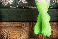 Foot overhang from the sofa in green socks Royalty Free Stock Photography