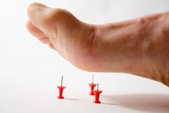Foot Pain. Foot stepping on tacks Stock Photo