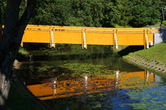Foot-path bridge and its reflection in water. Stock Image