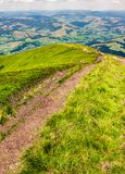 Foot path down the grassy hillside. Location mountain Gymba, TransCarpathia, Ukraine. tourists climbing hill in the distance. great summer outdoor activities Royalty Free Stock Images