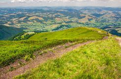 Foot path down the grassy hillside. Location mountain Gymba, TransCarpathia, Ukraine. tourists climbing hill in the distance. great summer outdoor activities Stock Photo