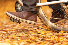 Foot on pedal of bicycle in park. Royalty Free Stock Photos