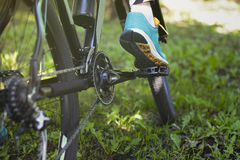 Foot on pedal of bicycle in park, active summer Royalty Free Stock Image