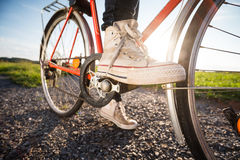 Foot on pedal. Wide shot of the foot on pedal of retro orange bicycle at sunset in countryside. Active summer. Vintage feeling. Low depth of field. Strong sun Royalty Free Stock Photography