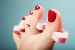 Foot pedicure applying red toenails on blue Stock Photo