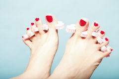 Foot pedicure applying red toenails on blue Royalty Free Stock Photography