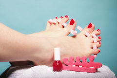 Foot pedicure applying red toenails on blue Royalty Free Stock Images